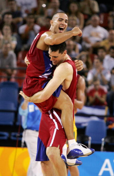 Athens, GREECE: Puerto Rico's Carlos Arroyo (L) jumps in the arms of teammate Daniel Santiago (R) following their victory over Australia, 21 August 2004, during the Olympic Games Men's Basketball preliminaries at Helliniko indoor arena in Athens. Daniel Santiago scored 20 points and Elias Ayuso added 18 to lead Puerto Rico past Australia 87-82, an Olympic men's basketball preliminary victory that ensured Puerto Rico a quarter-final berth. AFP PHOTO/DON EMMERT (Photo credit should read DON EMMERT/AFP/Getty Images)