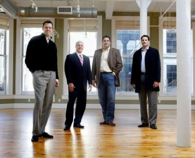 From left, Jeff Baker, David Wiener, Mike Peplowski, and Matt Steigenga stand in a renovated suite on the second floor of Aldrich Place at 80 Ottawa Ave. NW. Baker, Peplowski, and Steigenga make up Sixty North Ventures, a company which specializes in historic restorations. North Ventures recently purchased 139 Pearl Street, the building that holds Flanagan's, 87 Monroe Center and 80 Ottawa Avenue. (Emily Zoladz | The Grand Rapids Press)